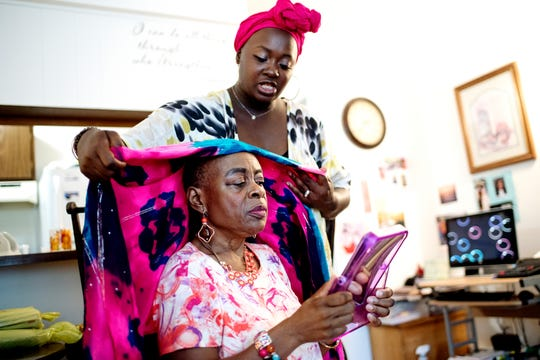 UnCovered LLC founder Nekeyta Brunson shows client Annie Hicks ways to style a head wrap at Hicks' home during a consultation on Friday, Aug. 3, 2018, in Lansing. Brunson is the founder of the business that offers solutions and support to women living with hair loss.