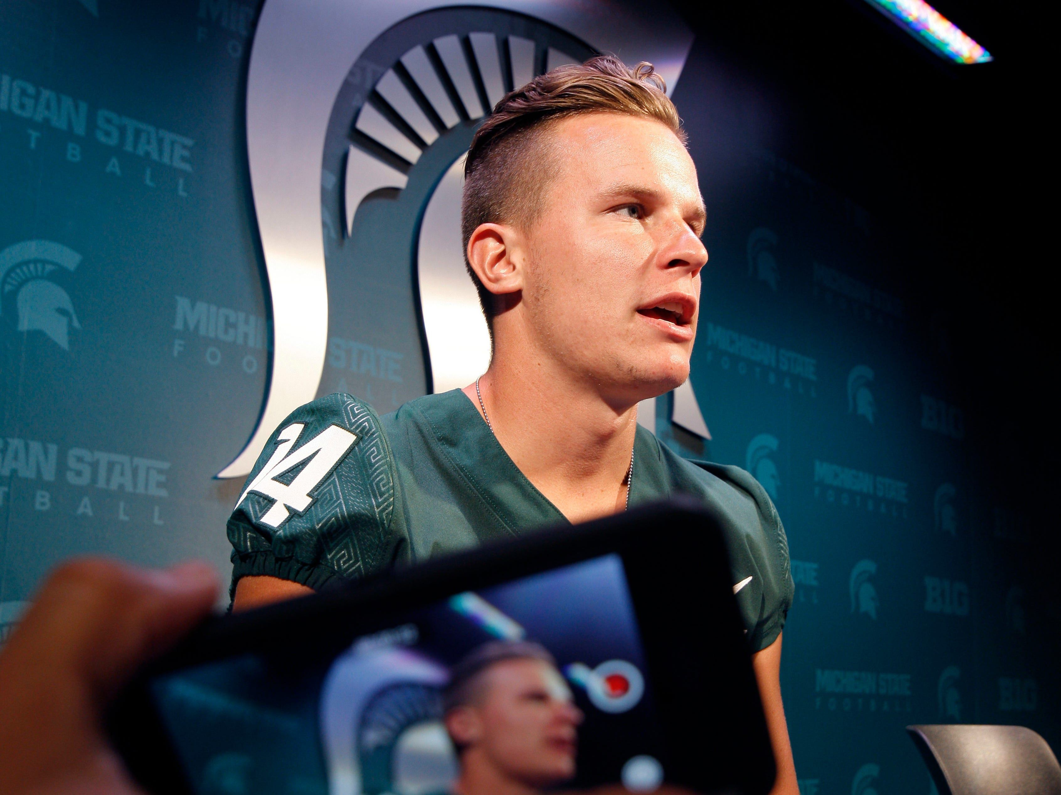 Michigan State quarterback Brian Lewerke talks with reporters during the team's NCAA college football media day, Monday, Aug. 6, 2018, in East Lansing, Mich.