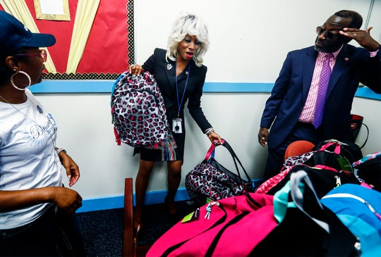 Achievement School District new chief Sharon Griffin (middle) grabs donated backpacks full of supplies to students at Georgian Hills Achievement Elementary on the first day of school.