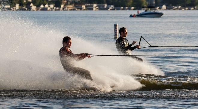 Barefoot skiers Jake Wieseckel (left) of Sussex and Jacob Gresser of Nashotah speed past during the Pewaukee Lake Water Ski Club's weekly show at Lakefront Park on Thursday, Aug. 2. A new state law has eliminated the requirement for skiers to have an observer in the boat. Now, skiers can practice their hobby as long as the boat is equipped with a mirror with a wide-angle view.
