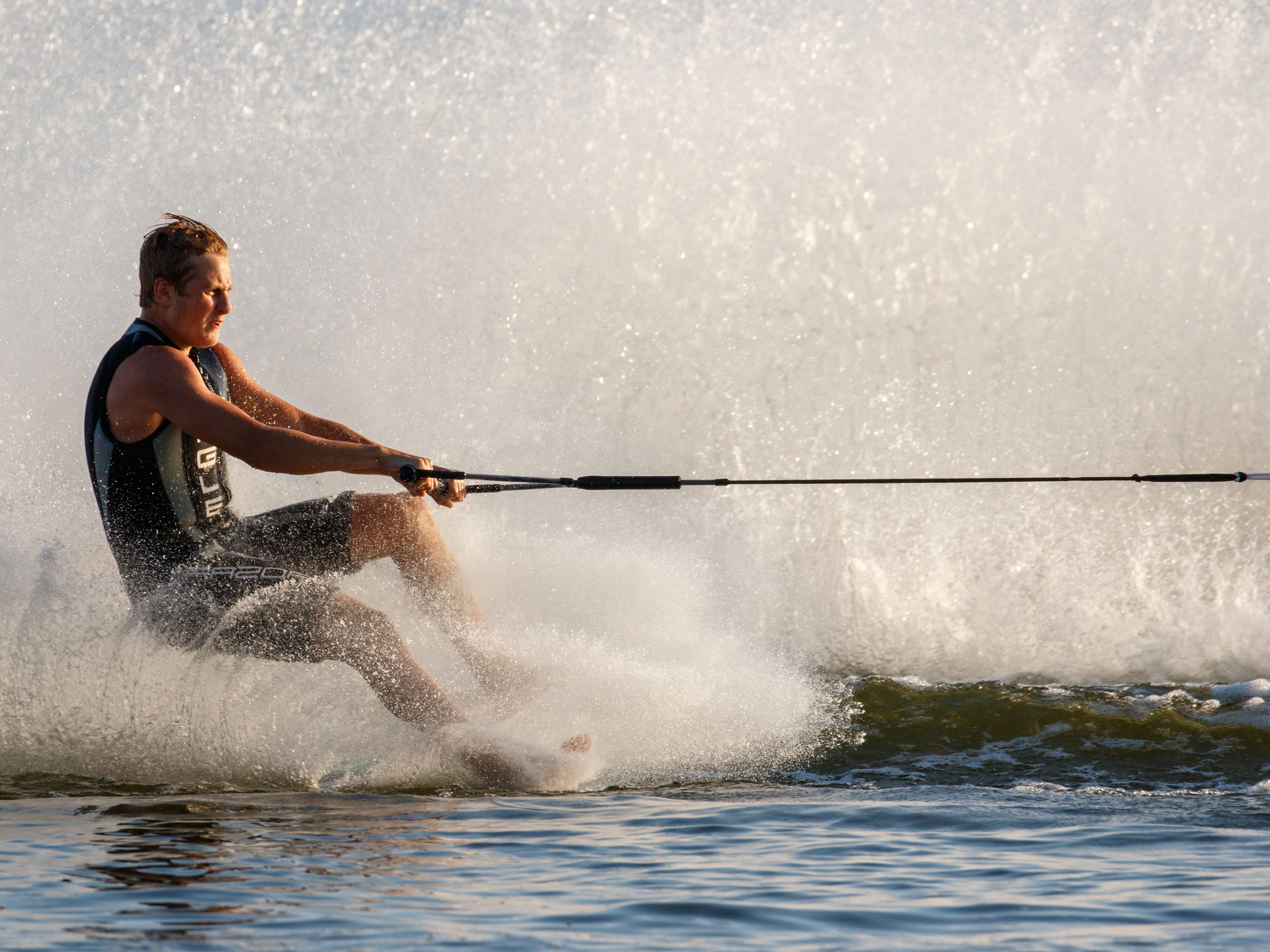 Barefoot skier Nick Kasic of West Bend speeds past during the Pewaukee Lake Water Ski Club's weekly show at Lakefront Park on Thursday, August 2, 2018.