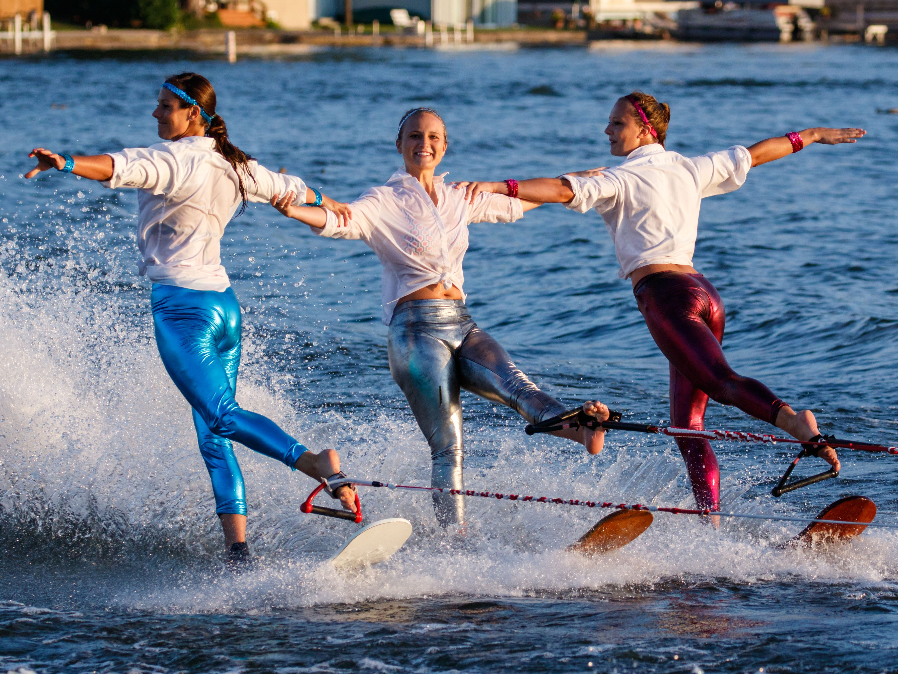 Skiers (from left) Amanda Norris of Oconomowoc, Taylor Barry of Wauwatosa and Kristie Regal of Oconomowoc perform on swivel skis during the Pewaukee Lake Water Ski Club's weekly show at Lakefront Park on Thursday, August 2, 2018.