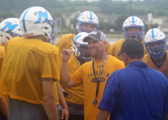Mukwonago head coach Mike Gnewuch directs the offensive huddle during a practice on August 6.
