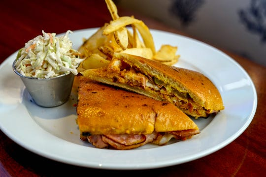 The Smugglers Sandwich is an Everglades-style Cuban sandwich with fried grouper, Black Forest ham and Swiss cheese with pickles and Firetail aioli at The Pearl Steak & Seafood Restaurant in North Naples.