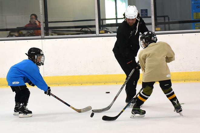 Drew Cameron, 5, and Charlie Hoyt, 7, try to steal the puck from coach Adam McHugh during youth hockey camps Monday morning at Lou & Gib Reese Ice Arena in Newark. Monday was the first day of the season at the ice rink on the fresh ice.