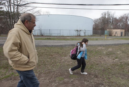 The Fair Lawn well fields that sit in a Superfund site shown in the background as Moreno Siano walks his granddaughter Kayla Stafford, 9, home from school on March 18, 2016.