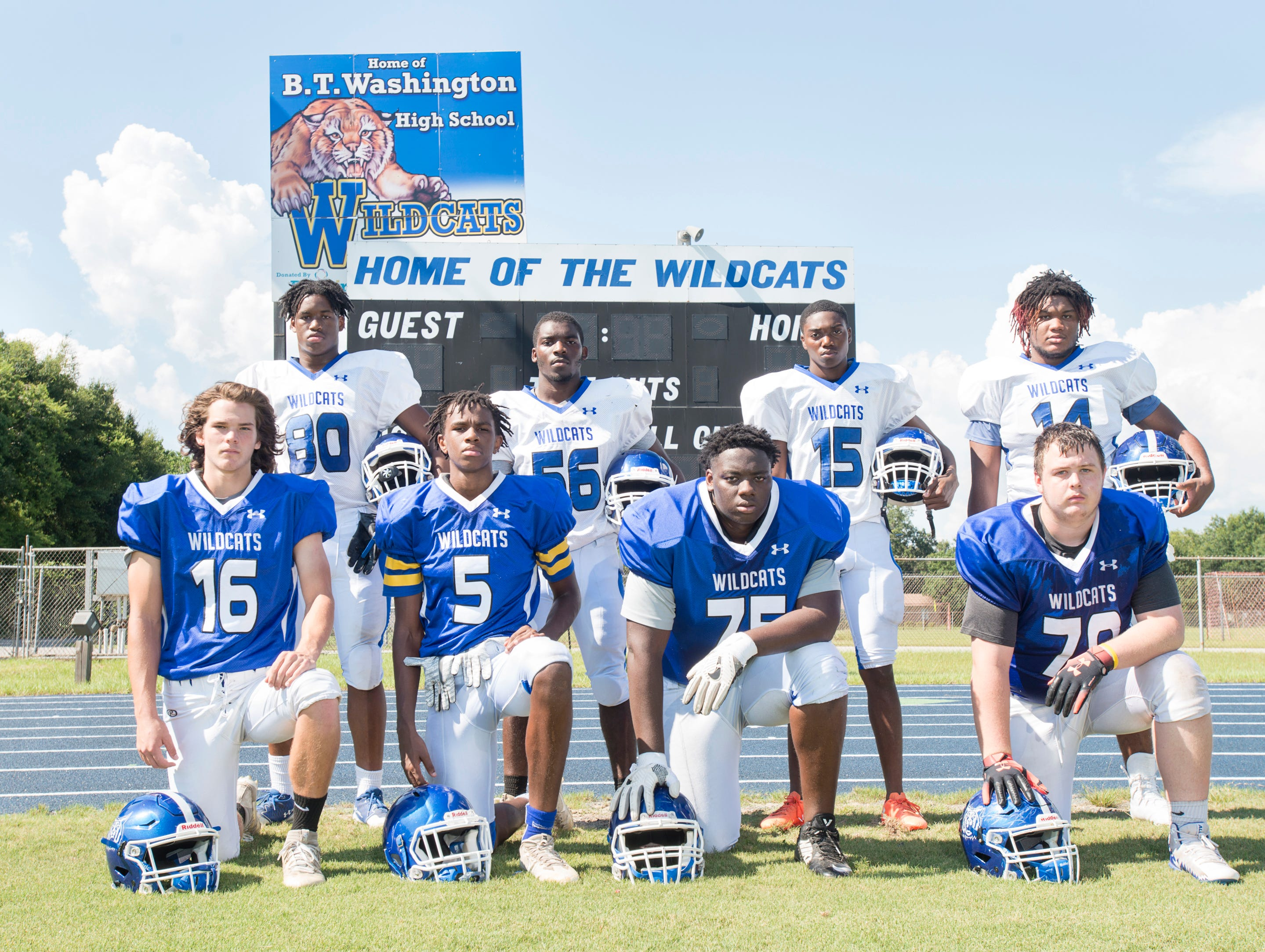 Front row from left: Joe Slattery (16), Erick Smith (5), Timothy Robinson  (75), Michael Hynes (70) and back row from left: Eric Thomas (80), Shawn Roberts (56), Darion Mcshan (15), Amari Severson (14) pose for a photo during football practice at Booker T. Washington High School in Pensacola on Monday, August 6, 2018.