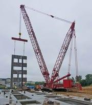 A Manitowoc MLC300 lattice crawler crane works at a job site.