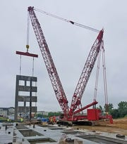 A Manitowoc MLC300 lattice crawler crane works at a job site.