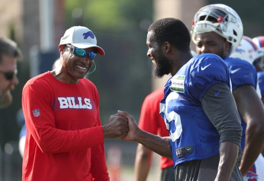 Bills defensive coordinator Leslie Frazier is greeted by tight end Charles Clay during practice.