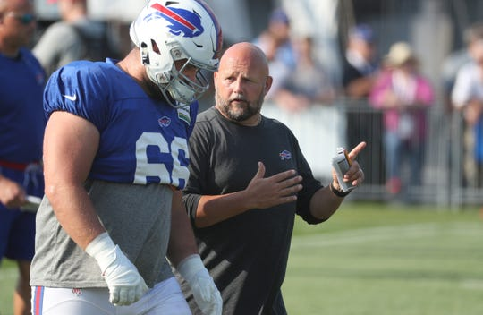 Bills offensive coordinator Brian Daboll makes a point to center Russell Bodine during training camp.