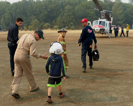 Helicopter pilot Brandon Sheets chats Monday with 5-year-old Carter Garrison as he shakes the boy's hand.