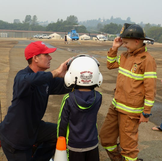 Tim Stepanovich, Cal Fire air operations branch director, adjusts Carter Garrison's flight helmet as Kenny Garrison asks a question.