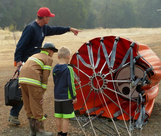 Tim Stepanovich shows a collapsible bucket to Kenny and Carter Garrison. The buckets can contain more than 600 gallons of water.