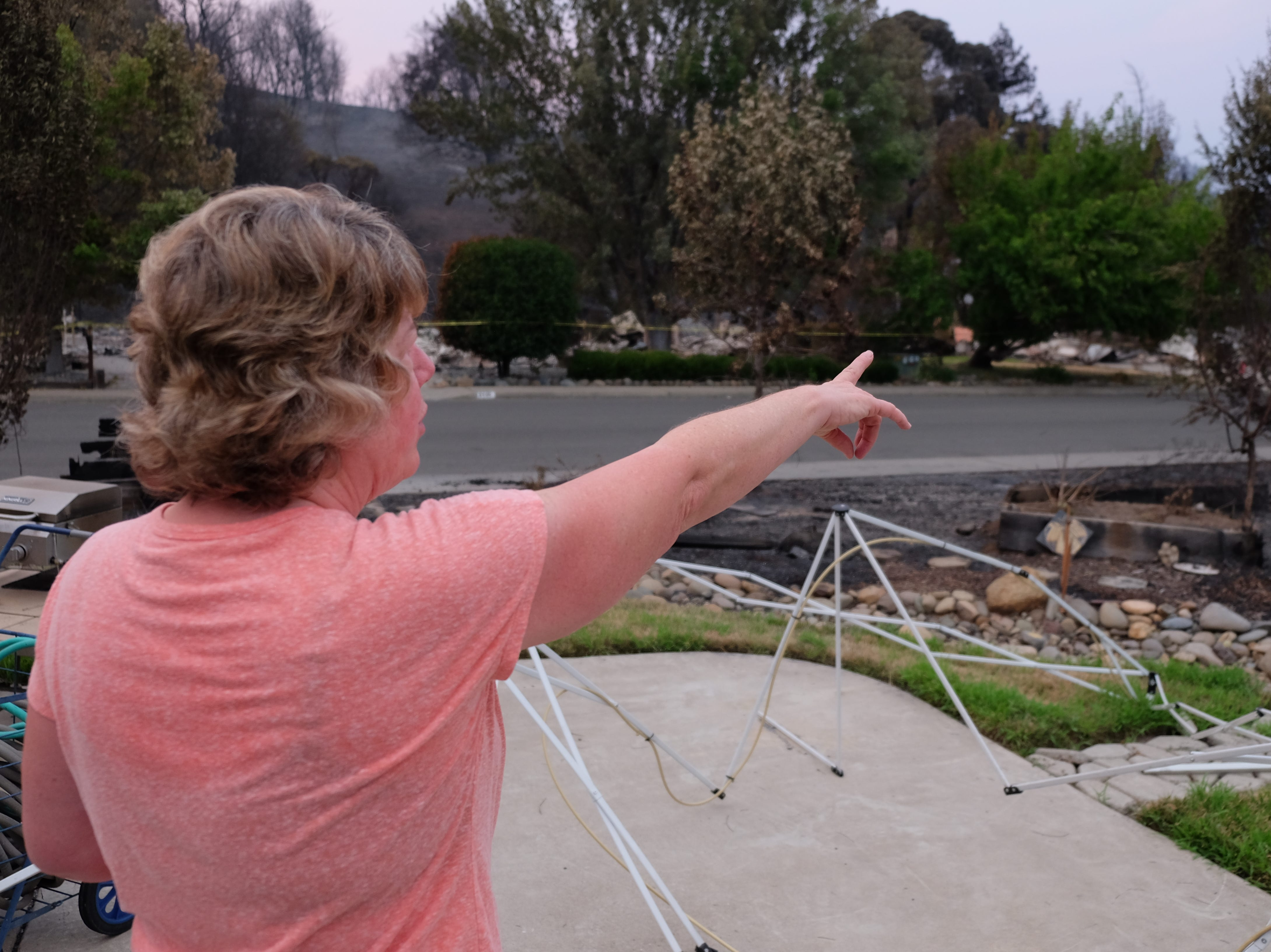 Alisa Robinson points at neighboring homes burned to the ground while describing the neighborhood which saw many residents displaced by the Carr Fire in Redding, California.