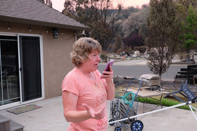 Alisa Robinson speaks with a utility company to get power restored at their Redding home. The Robinsons, former Salem residents, fled their residence during the Carr Fire which avoided major damage yet leveled homes on all sides.