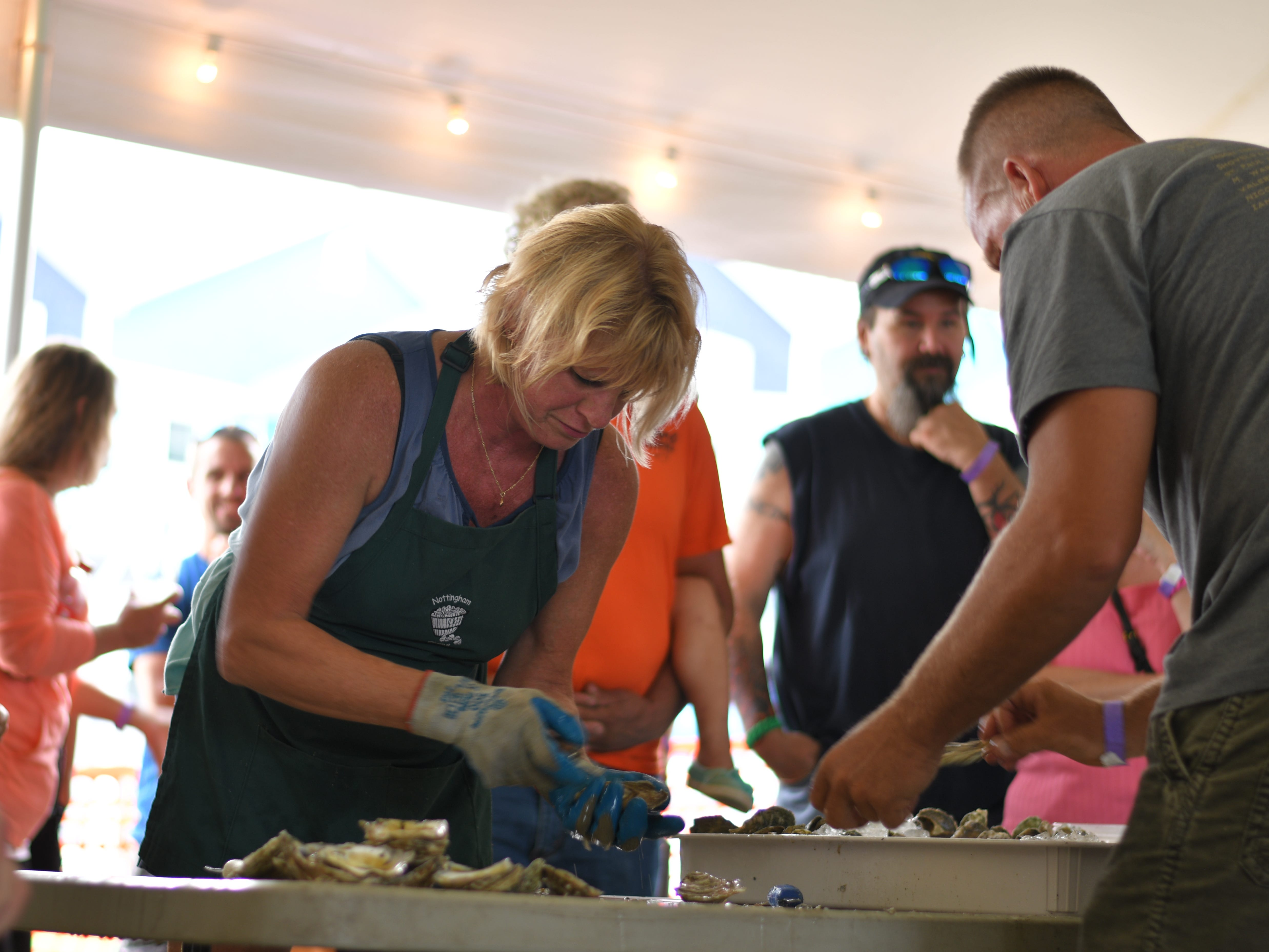 Amy Nottingham shucks oysters for her partner, Scott Simms, at the 3rd Annual Oyster Eating Contest.
