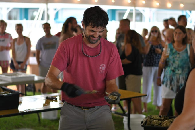 Chris Buck shucks an oyster at the 3rd Annual Shuck-N-Suck Oyster Eating Contest on  Aug. 3 at the Oyster Farm in Cape Charles.