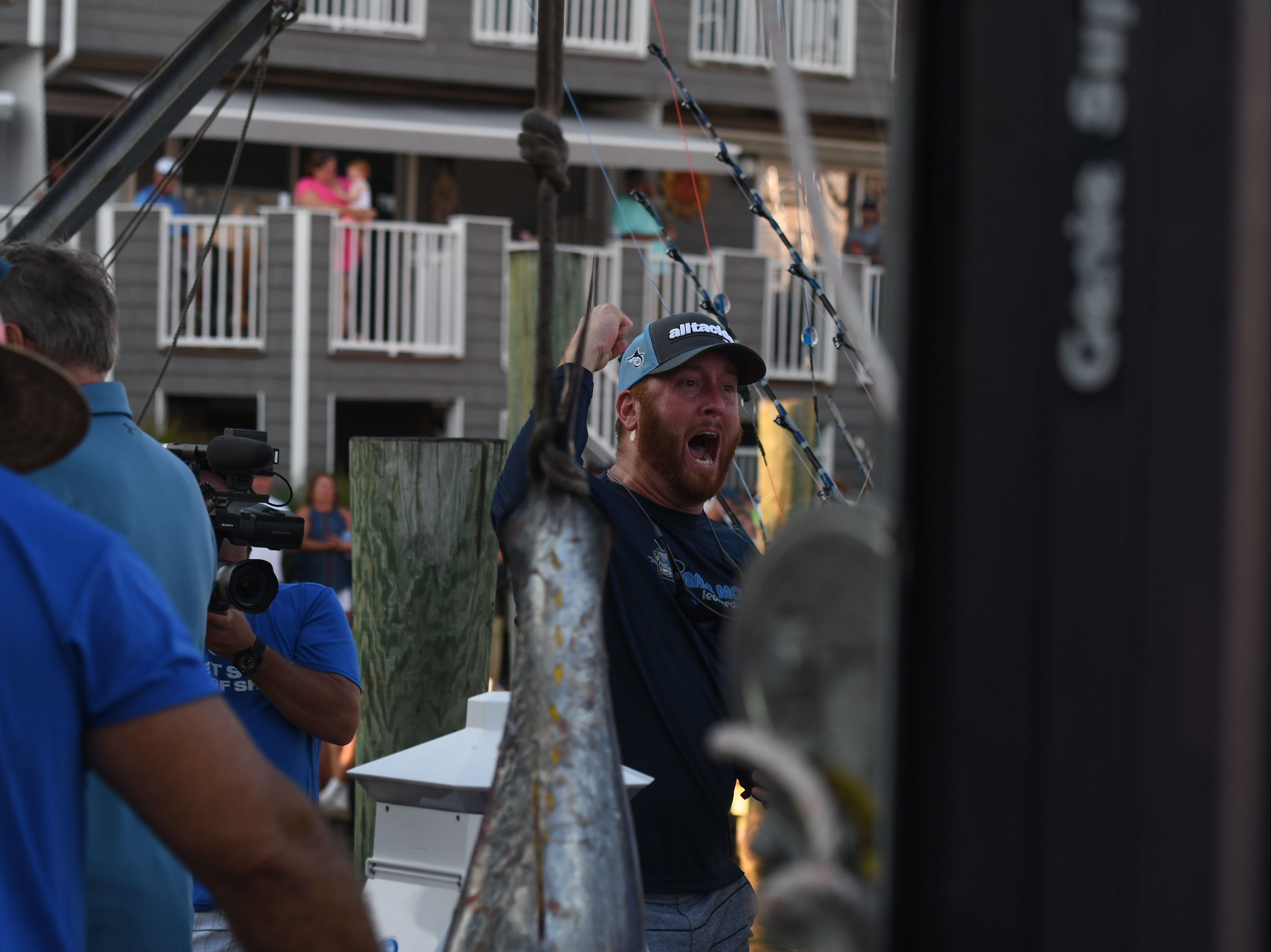 A crew member from aboard the Brass Monkey cheers as their 71lb tuna takes over first place on Monday, August 6, 2018 during the 45th Annual White Marlin Open in Ocean City, Md.