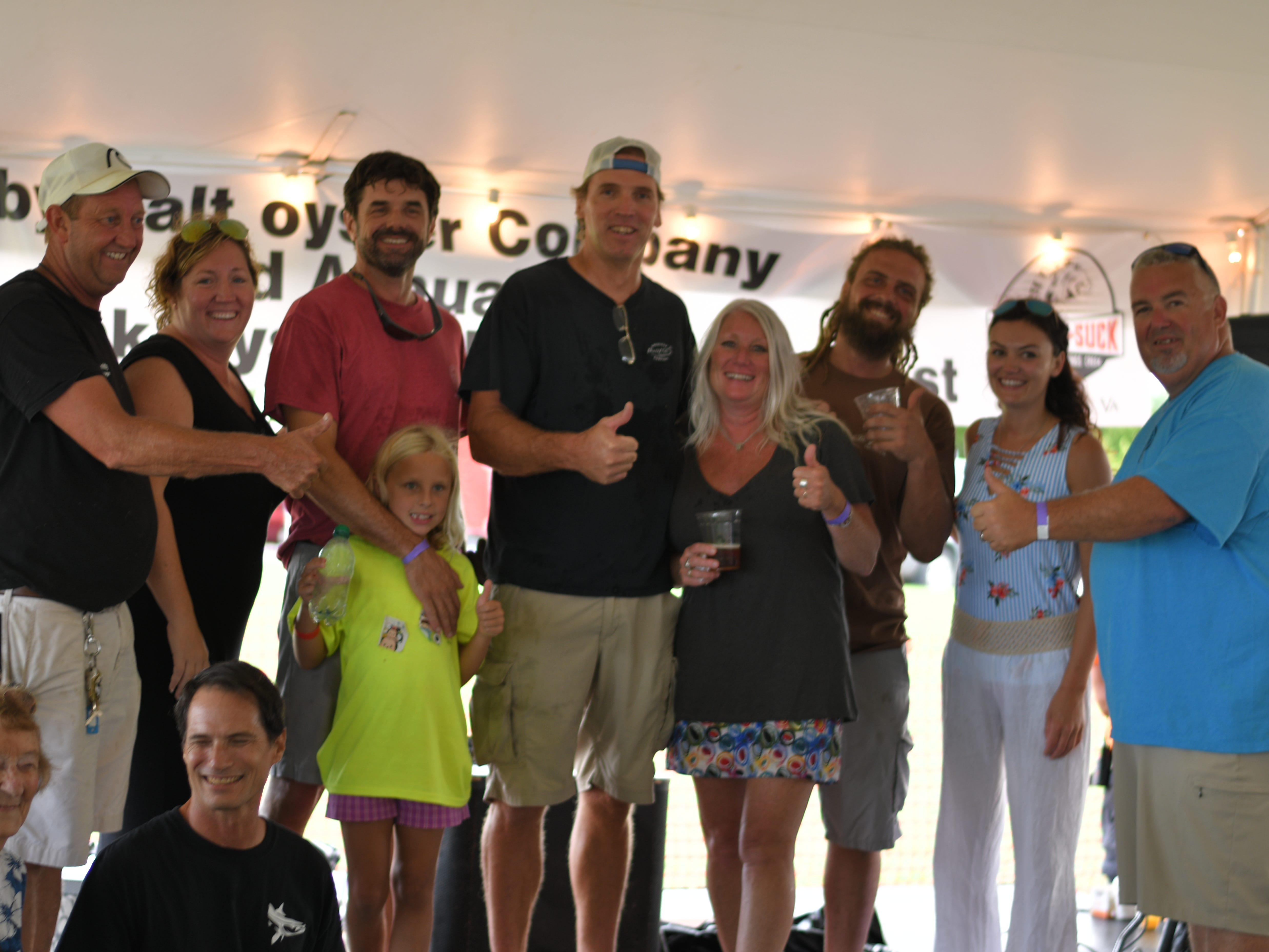 From left: Cape Charles Mayor Smitty Dize; first place winners Tiffany Mohr and Chris Buck; second place winners Joe Peirson and Sally Lewin; third place winners Scott Wivell and Rachel Savage; and announcer Flea Emily; pose for a picture after the 3rd Annual Oyster Eating Contest on Aug. 3 at the Oyster Farm in Cape Charles.