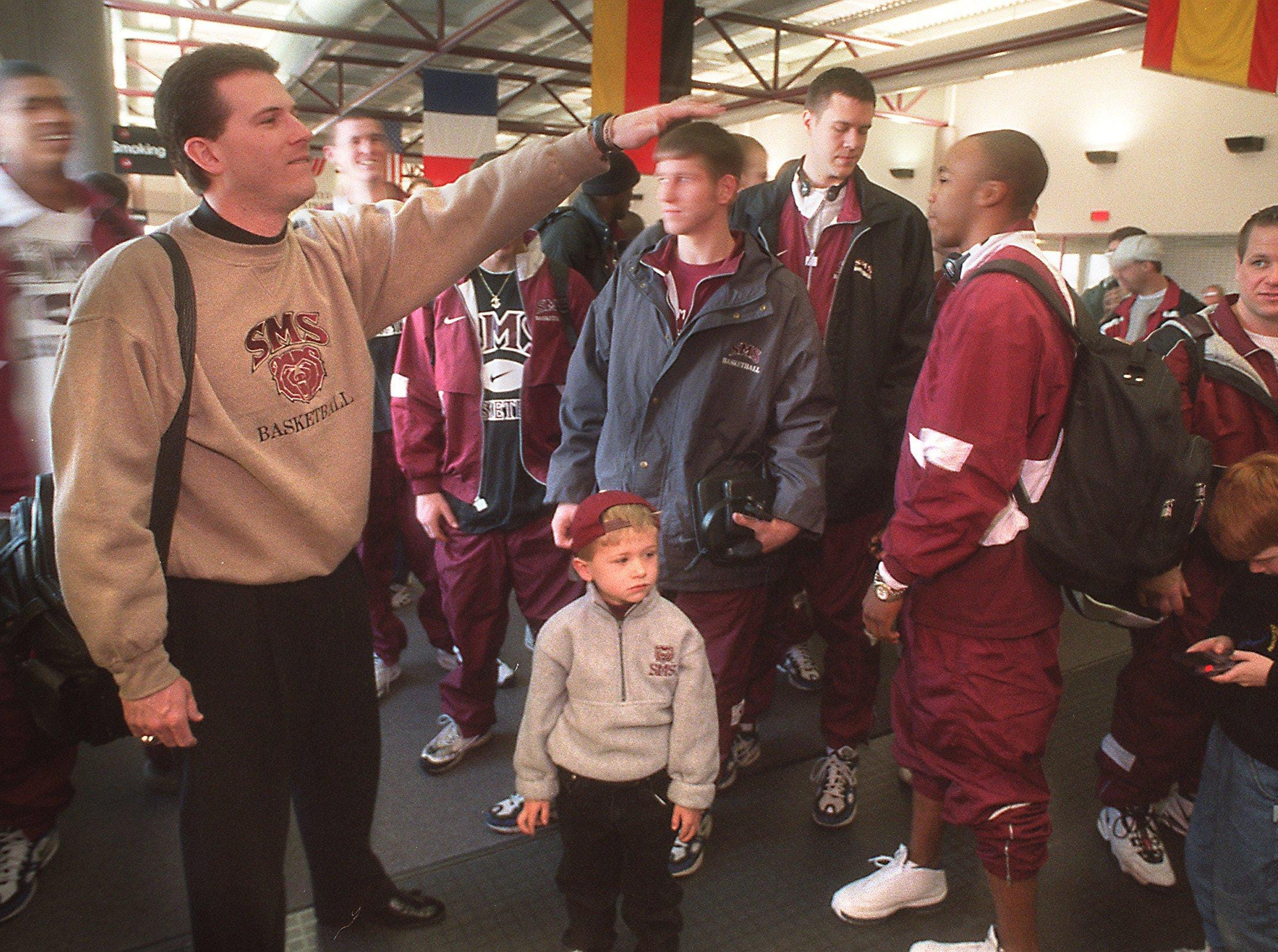 -  -news (22635) - SMS coach Steve Alford, (left) his son Bryce and the team leave the Springfield-Branson Regional Airport for Charlotte, N.C.  Bob Linder / News-Leader