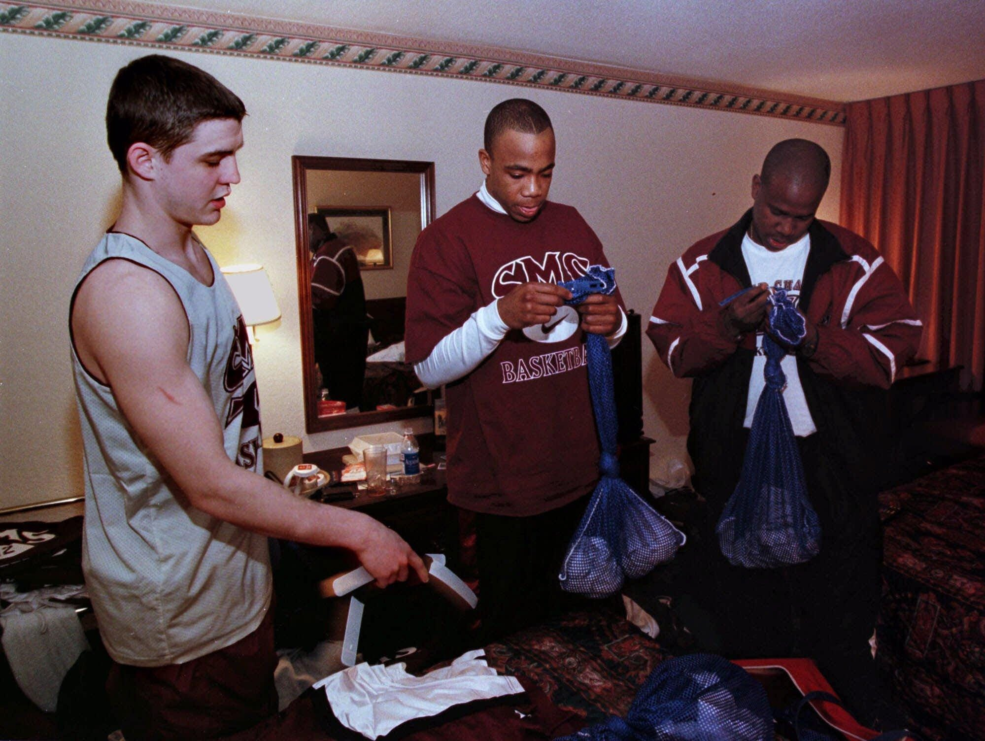 -  -SPECIAL TO THE SPRINGFIELD MISSOURI NEWS LEADER-- Southwest Missouri State basketball players Brandon Miller, left, and William Fontleroy, center, drop off dirty uniforms to team manager Mel Jessie, right, at the Clarion Hotel in Charlotte, N.C., Saturday, March 13, 1999. (Photo by Kevin White)
