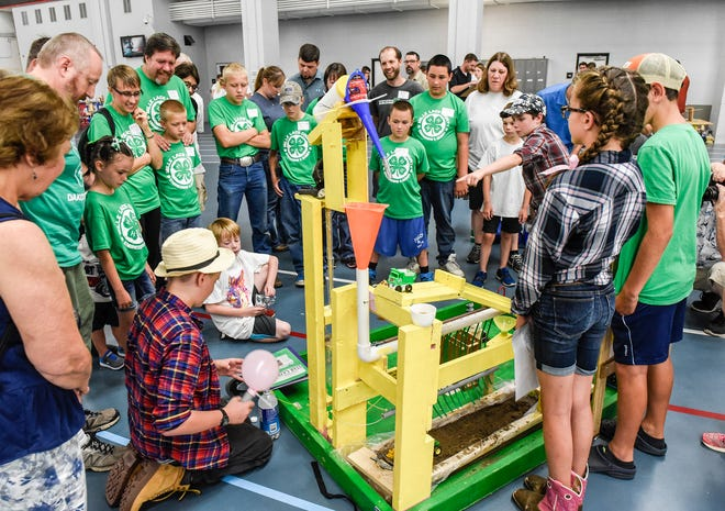 A team of inventors demonstrates its  machine during the Minnesota 4-H Engineering Design Challenge Monday, Aug. 6, at St. Cloud State University. The inventions are a complicated machine that performs a simple task.