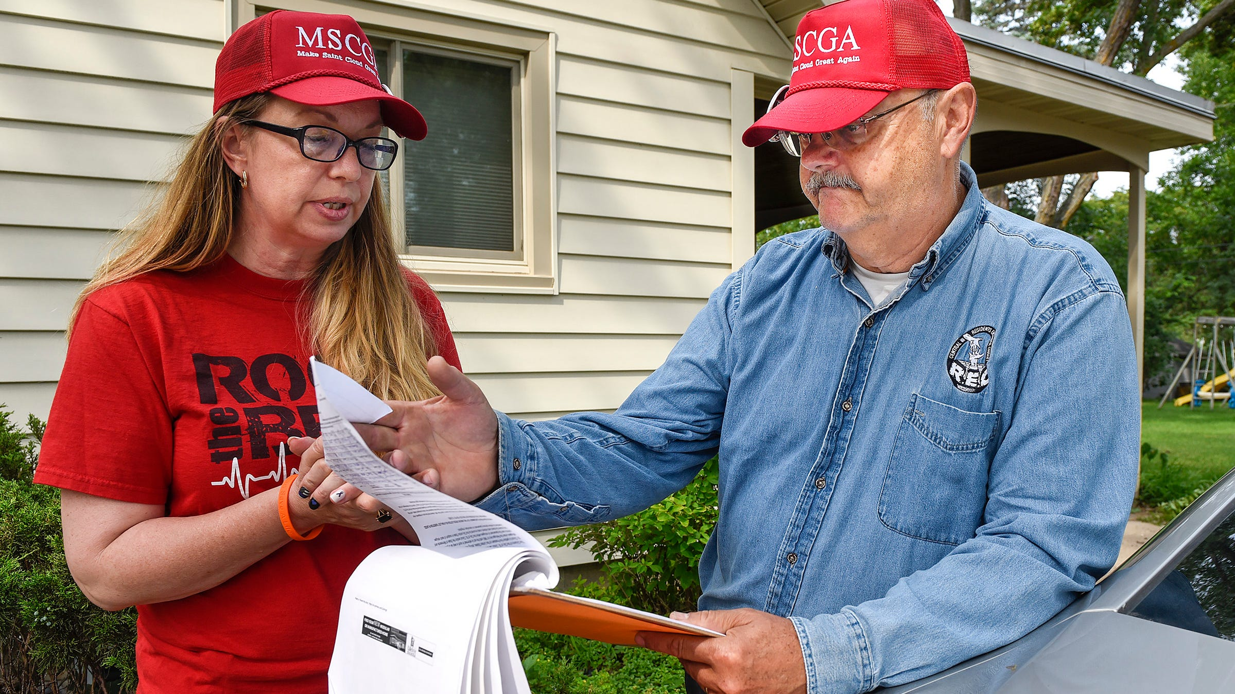 Liz Baklaich and John Palmer of the citizen group Concerned Community Citizens look at the signatures volunteers collected Friday, Aug. 3, to try to add a refugee resettlement resolution to the Nov. 6 ballot.