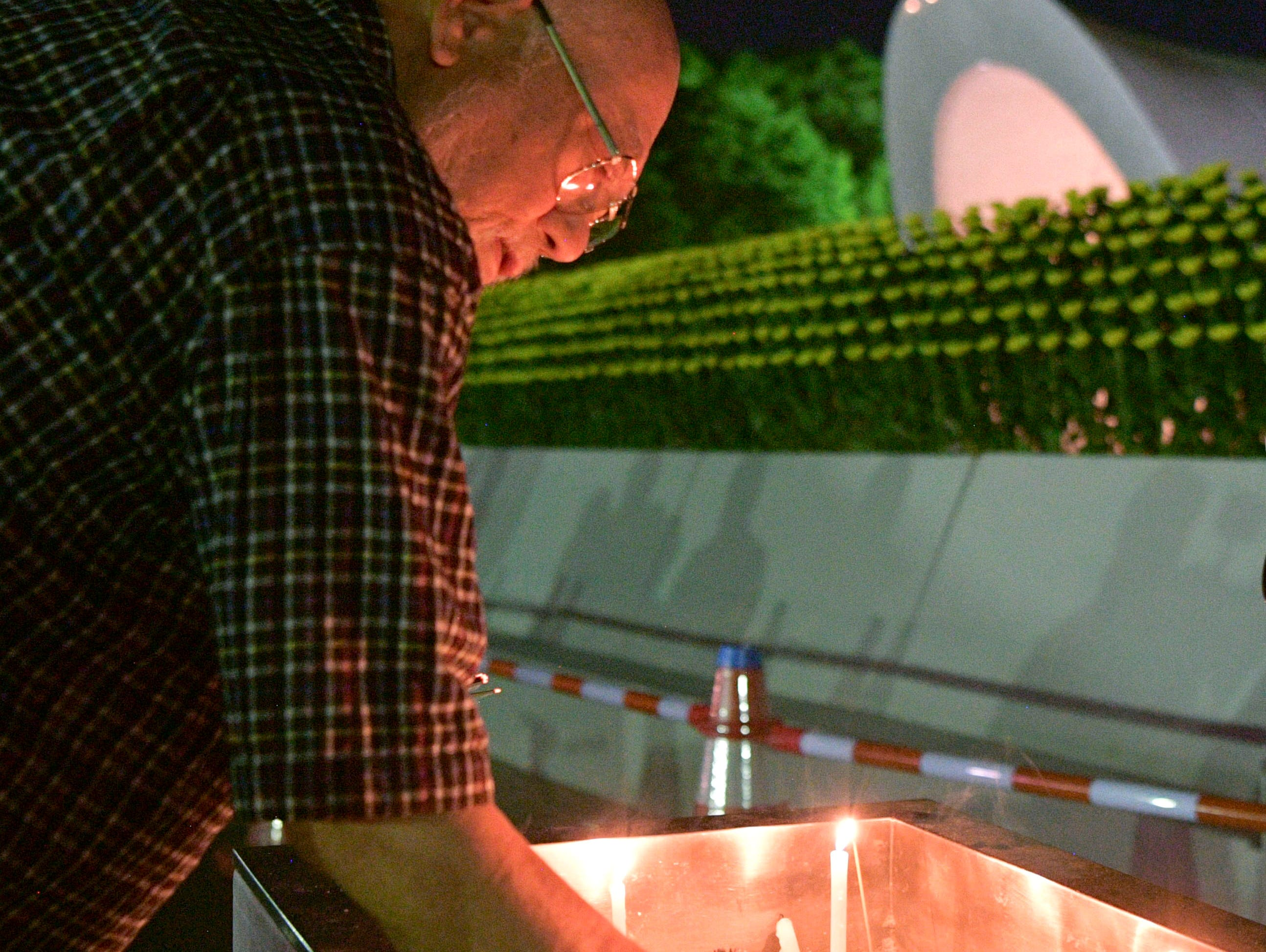 A man burns a stick of incense at the cenotaph dedicated to the victims of atomic bombing at Hiroshima Peace Memorial Park in Hiroshima, western Japan, early Monday, Aug. 6, 2018, marking the 73rd anniversary of the bombing.