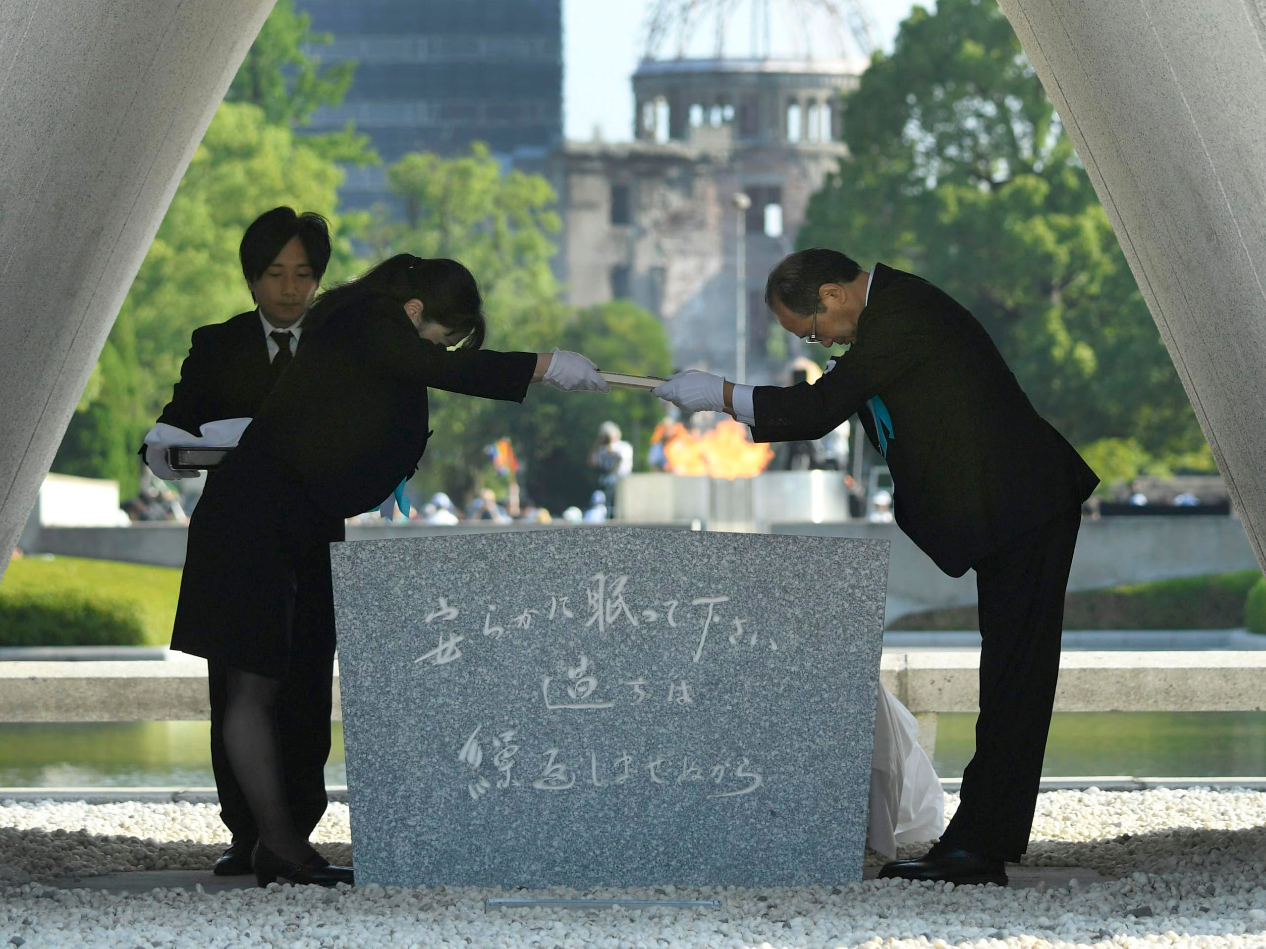 Hiroshima Mayor Kazumi Matsui, right, dedicates the list of the victims of atomic bombing to the cenotaph during a ceremony to mark the 73rd anniversary of the bombing at Hiroshima Peace Memorial Park in Hiroshima, western Japan, Monday, Aug. 6, 2018. Matsui raised concerns in his peace address about the rise of egocentric policies in the world and warned against the idea of nuclear deterrence as a threat to global security.