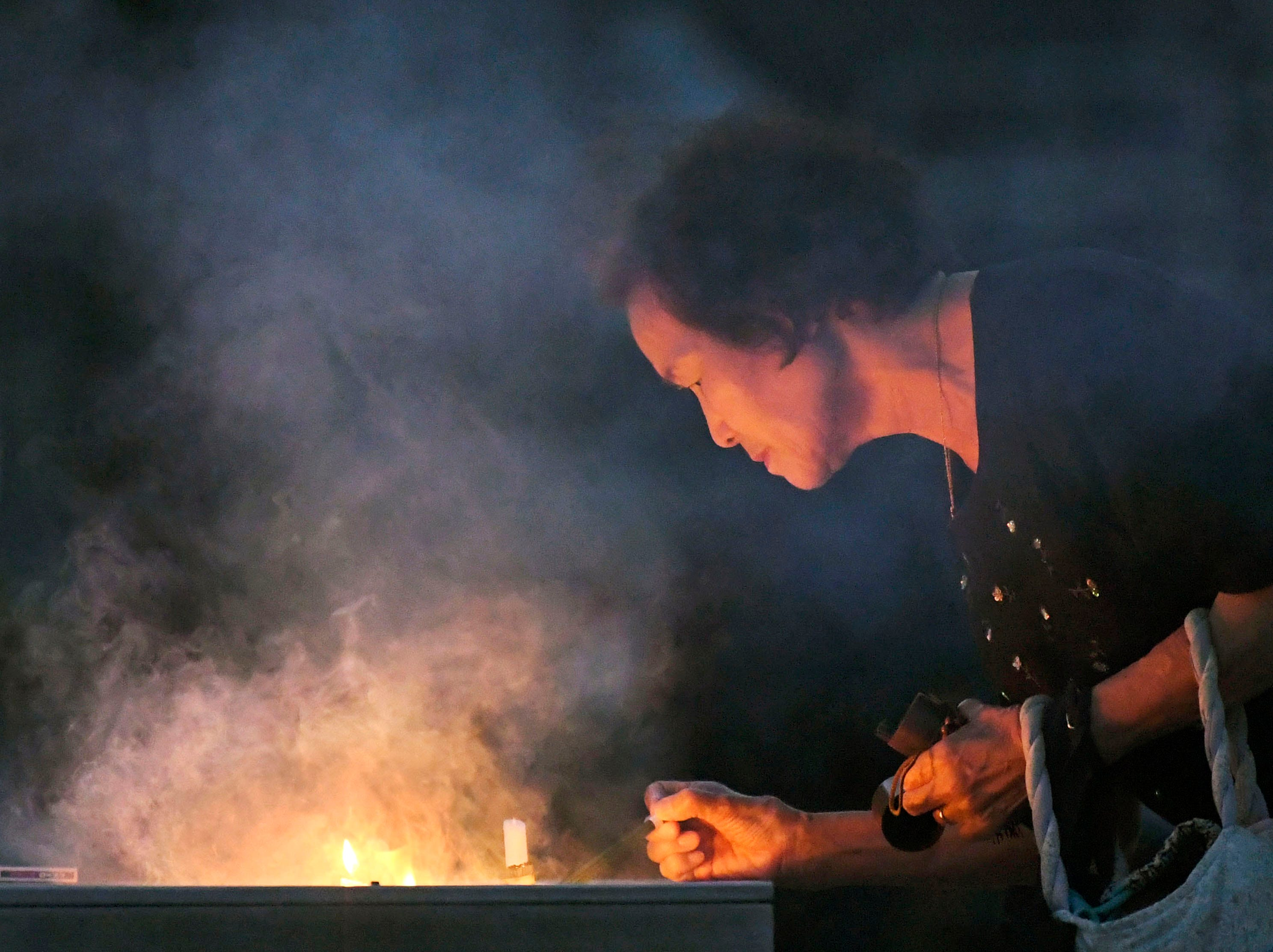 A woman burns a stick of incense at the cenotaph dedicated to the victims of atomic bombing at Hiroshima Peace Memorial Park in Hiroshima, western Japan, Monday, Aug. 6, 2018, marking the 73rd anniversary of the bombing.
