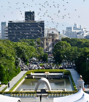 Doves fly over the cenotaph dedicated to the victims of the atomic bombing during a ceremony to mark the 73rd anniversary of the bombing at Hiroshima Peace Memorial Park in Hiroshima, western Japan, Monday, Aug. 6, 2018. The Atomic Bomb Dome is seen in center background.