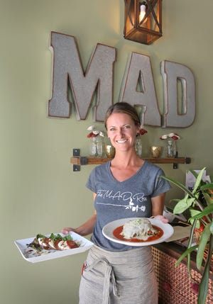 Meghan Davy, co-owner/manager of one of downtown Ventura's newest restaurants, The Mad Rose, holds a caprese salad and its popular lasagna.