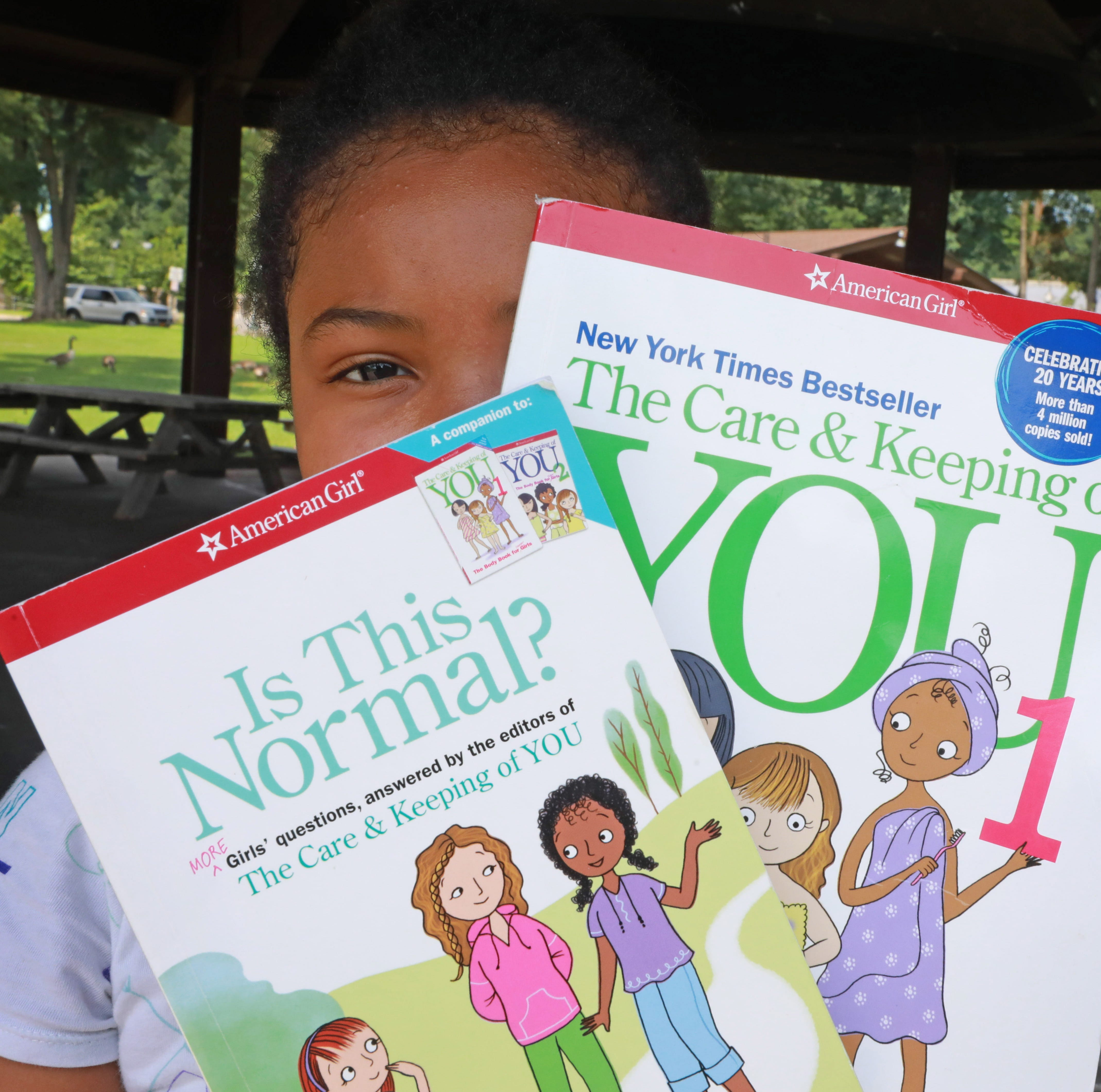 Kelly Mahecha,10, shows off the books she has been reading about becoming a tween at Riverfront Green Park in Peekskill Aug. 3, 2018. Shantae Mahecha, a high school teacher and a Peekskill resident plans to have a Period Party for her daughter.