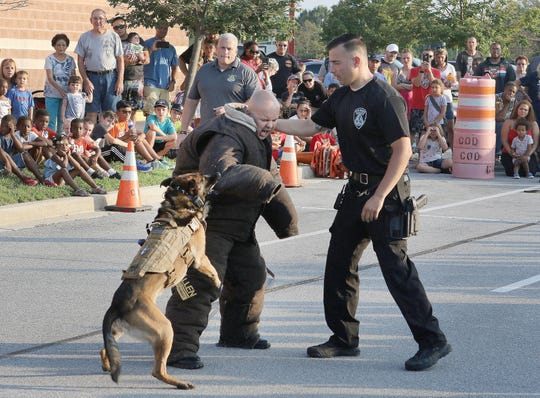 Gerome, a dog attached to the Dover Police Department's K-9 Unit, demonstrates how he stops someone in police custody (Cpl. Joe Bauer) from running while his partner Master Cpl. Frank Fioravanitii looks on.