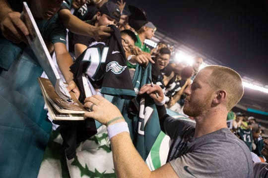 Eagles' Carson Wentz (11) signs autographs for fans after practice Sunday at Lincoln Financial Field.