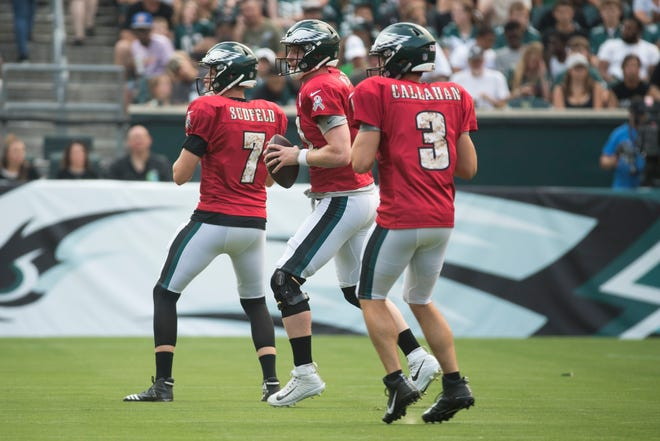 Eagles quarterbacks Nate Sudfeld (7), Carson Wentz (11), and Joe Callahan (3) warm up during the Eagles' first public practice Sunday at Lincoln Financial Field.