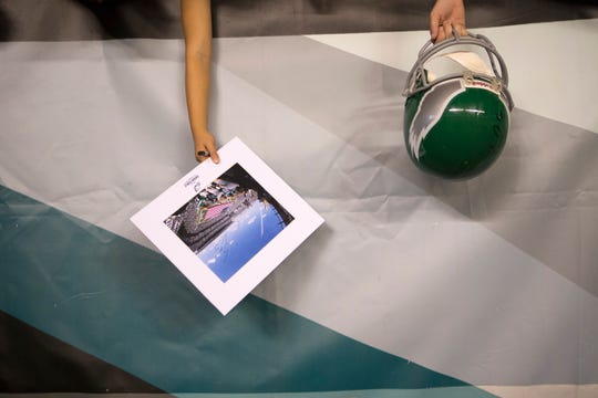 Eagles fans hold out memorabilia they want signed Sunday at Lincoln Financial Field.