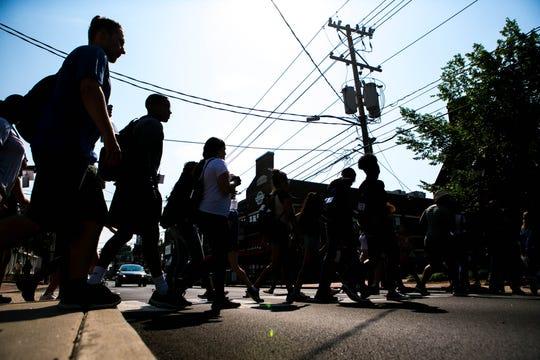 Pedestrians use a crosswalk at a traffic light on Main Street in Newark earlier this week.