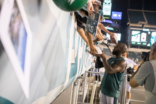 Eagles' Malcolm Jenkins (27) signs autographs for fans after practice in August 2018 at Lincoln Financial Field.