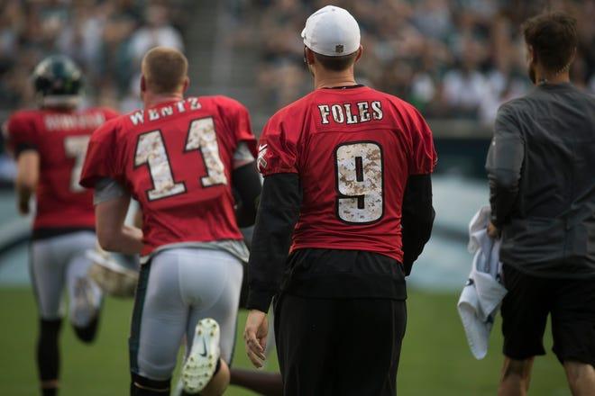 Eagles quarterback Nick Foles watches fellow quarterbacks Carson Wentz (11) and Nate Sudfeld (7) warm up before practice Sunday night.