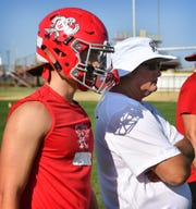 Holliday quarterback Jett Johnson talks with his father Frank Johnson during an August football practice.