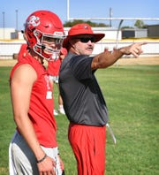 Holliday quarterback Jett Johnson gets some direction from assistant coach Kent Thomas during Monday's opening day of football practice.