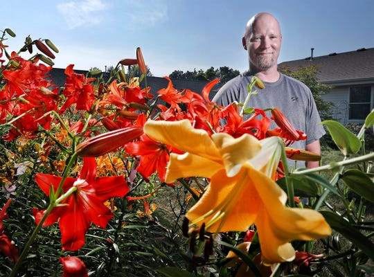 In this July 13, 2018 photo, Janesville resident David Whaley collects, displays and breeds lilies of all kinds in Janesville, Wis. Whaley discovered his lily-growing passion only three years ago. He recently took the stem of a pink and yellow Trogon to an international competition at the North American Lily Society, and came home with the Isabella Preston Best of Show trophy and three other high awards for the flower with 32 buds.