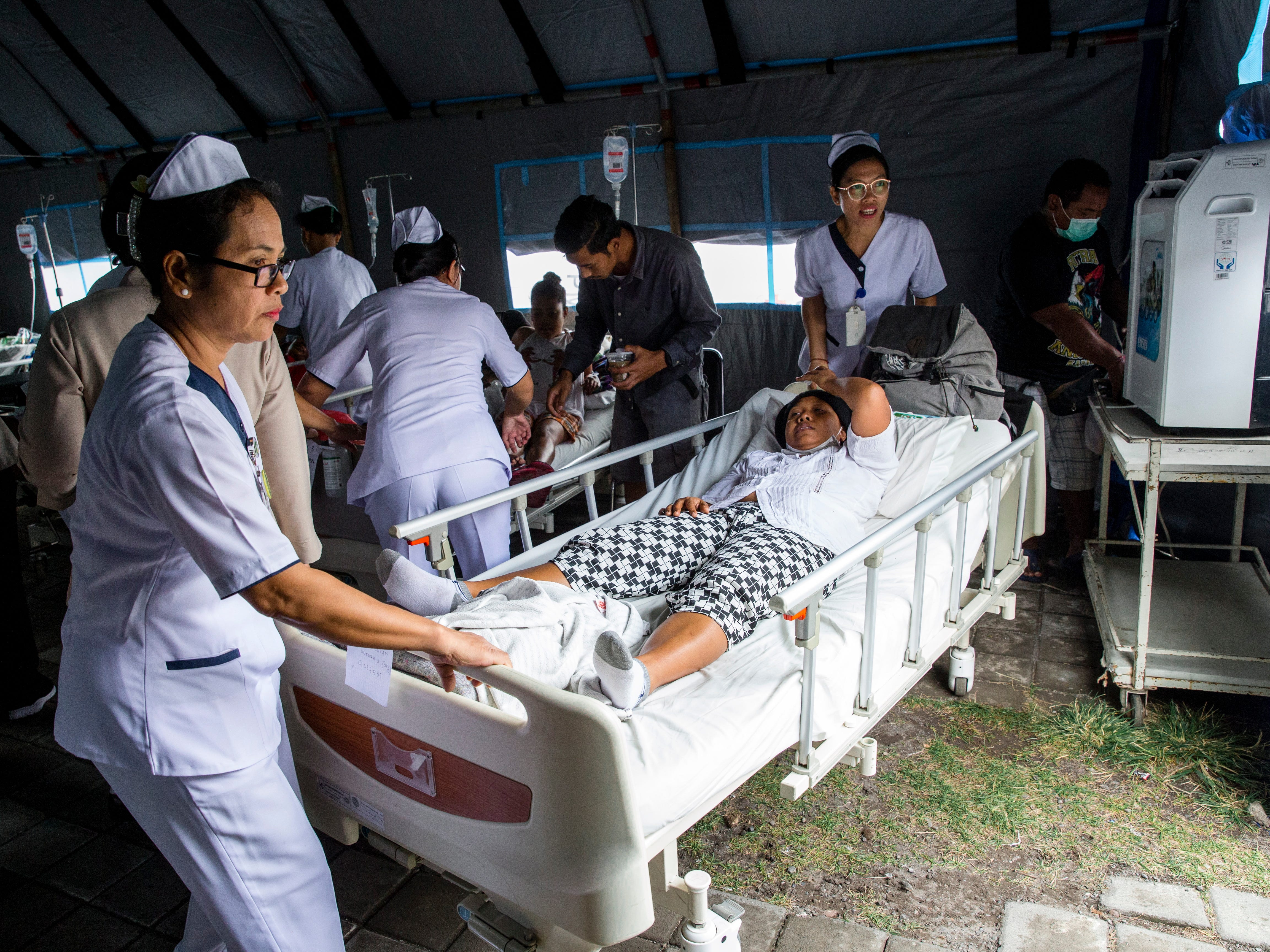 Hospital patients are moved to an emergency tent outside of a hospital building after an earthquake in Denpasar, Bali, Indonesia, on Aug. 6, 2018.