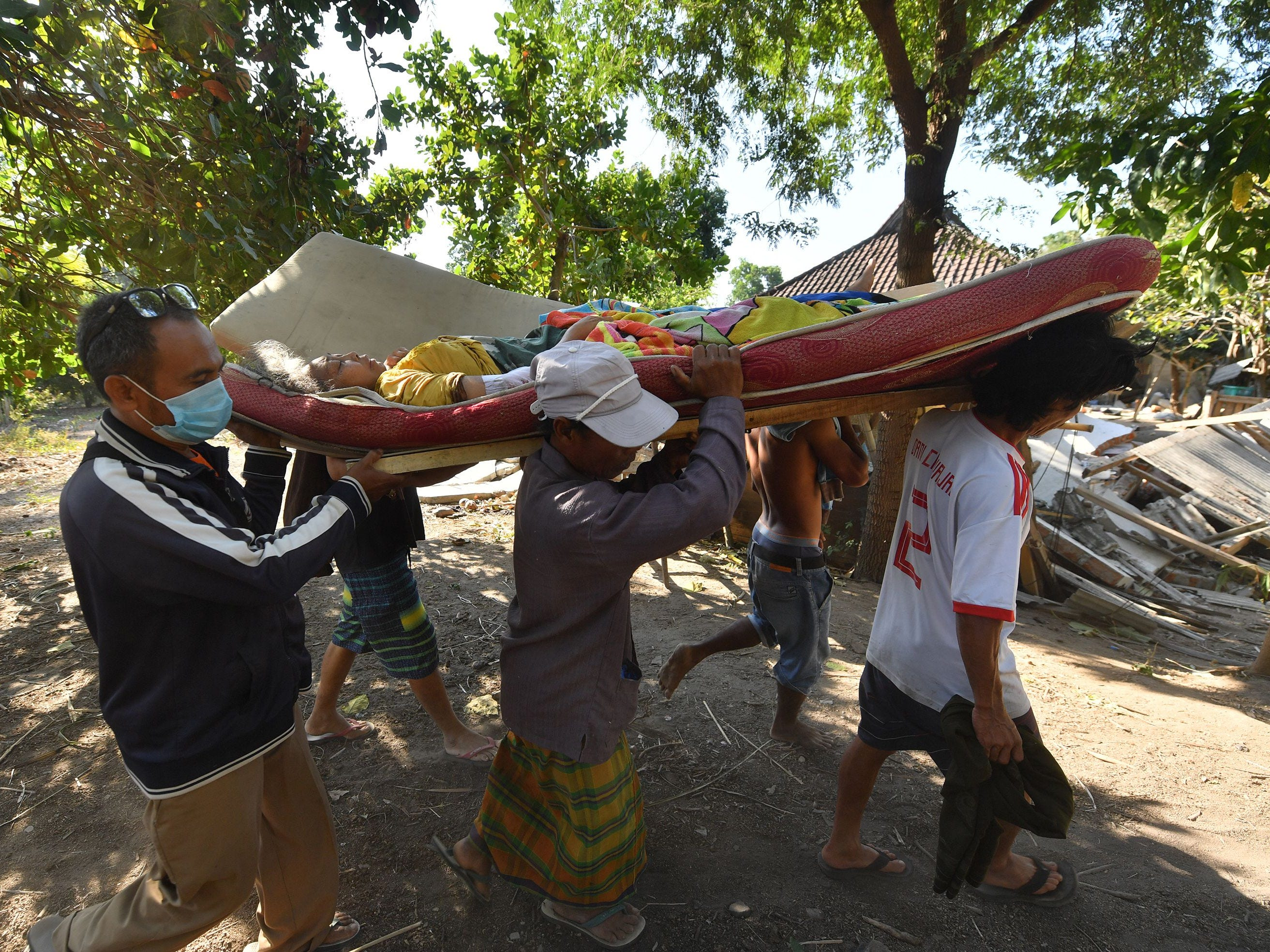 Indonesian people carry an injured woman in Pemenang, North Lombok on Aug. 6, 2018, the day after an earthquake struck the area.