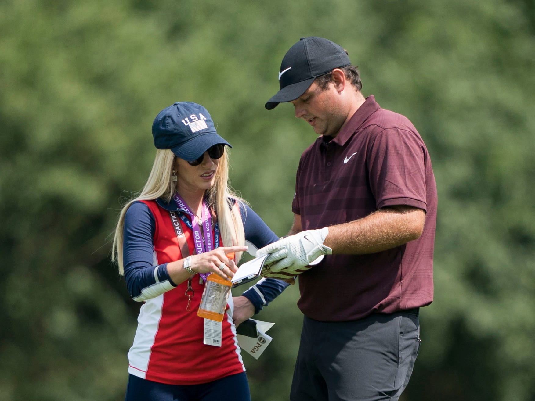 Patrick Reed talks to wife Justine Reed  on the first fairway.