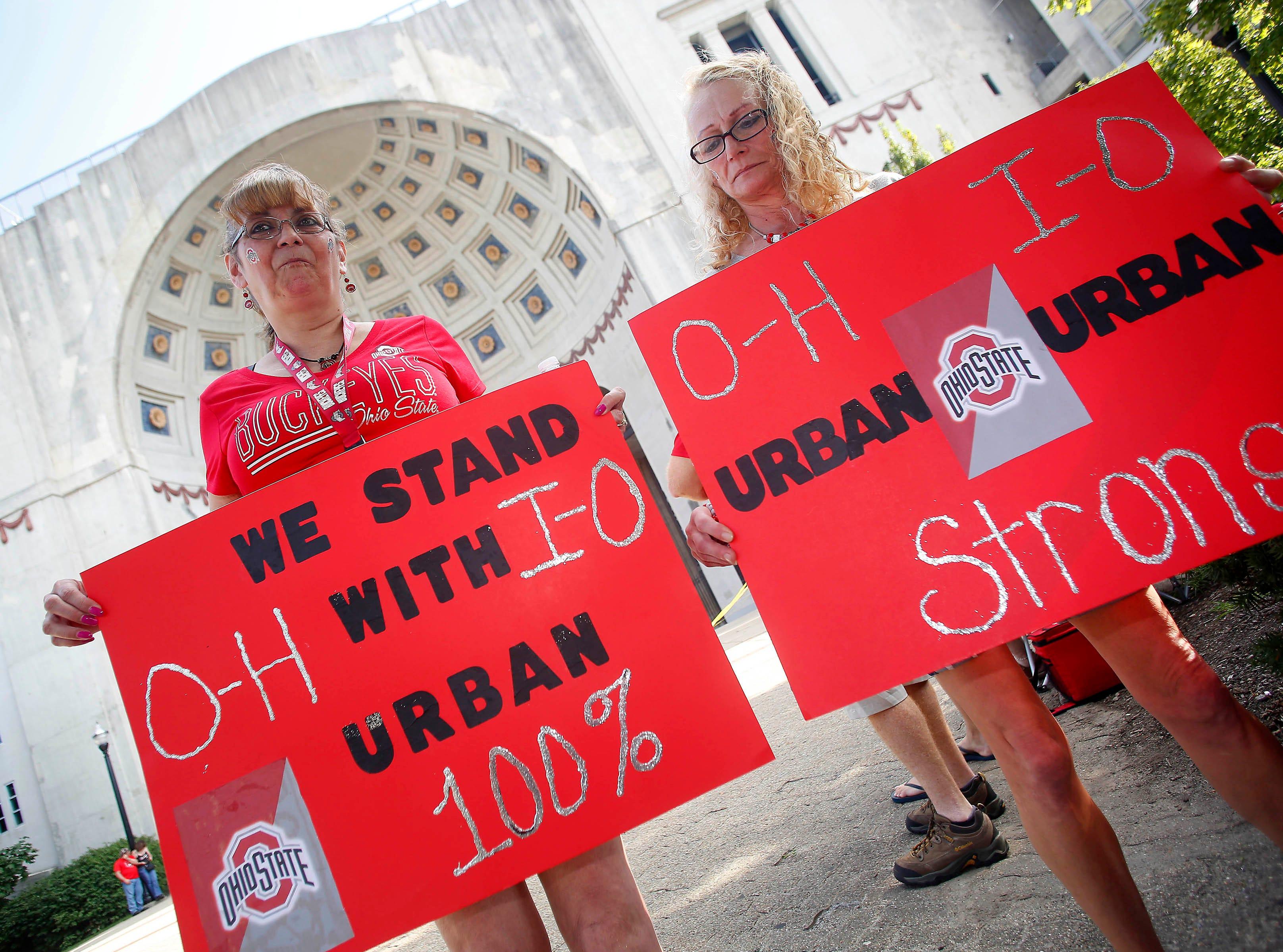 Tina Kear (left) and Lori Thompson of Upper Sandusky, Ohio, support Ohio State coach Urban Meyer at a rally held at Ohio Stadium.