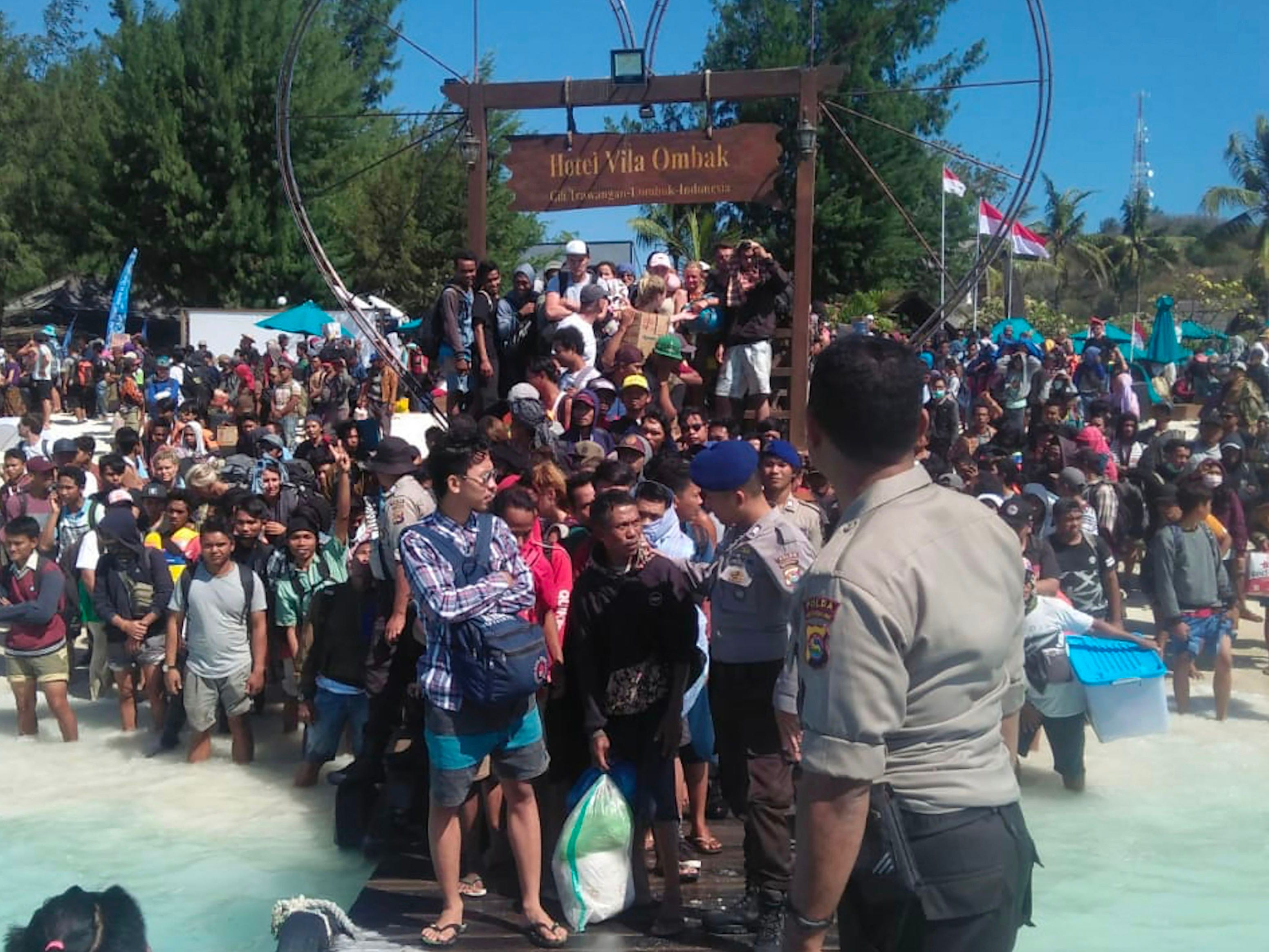 This handout picture taken on August 6, 2018 and released by Indonesia Water Police shows hundreds of people attempting to leave Gili Trawangan, north of neighboring Lombok island, a day after a powerful earthquake struck the area.