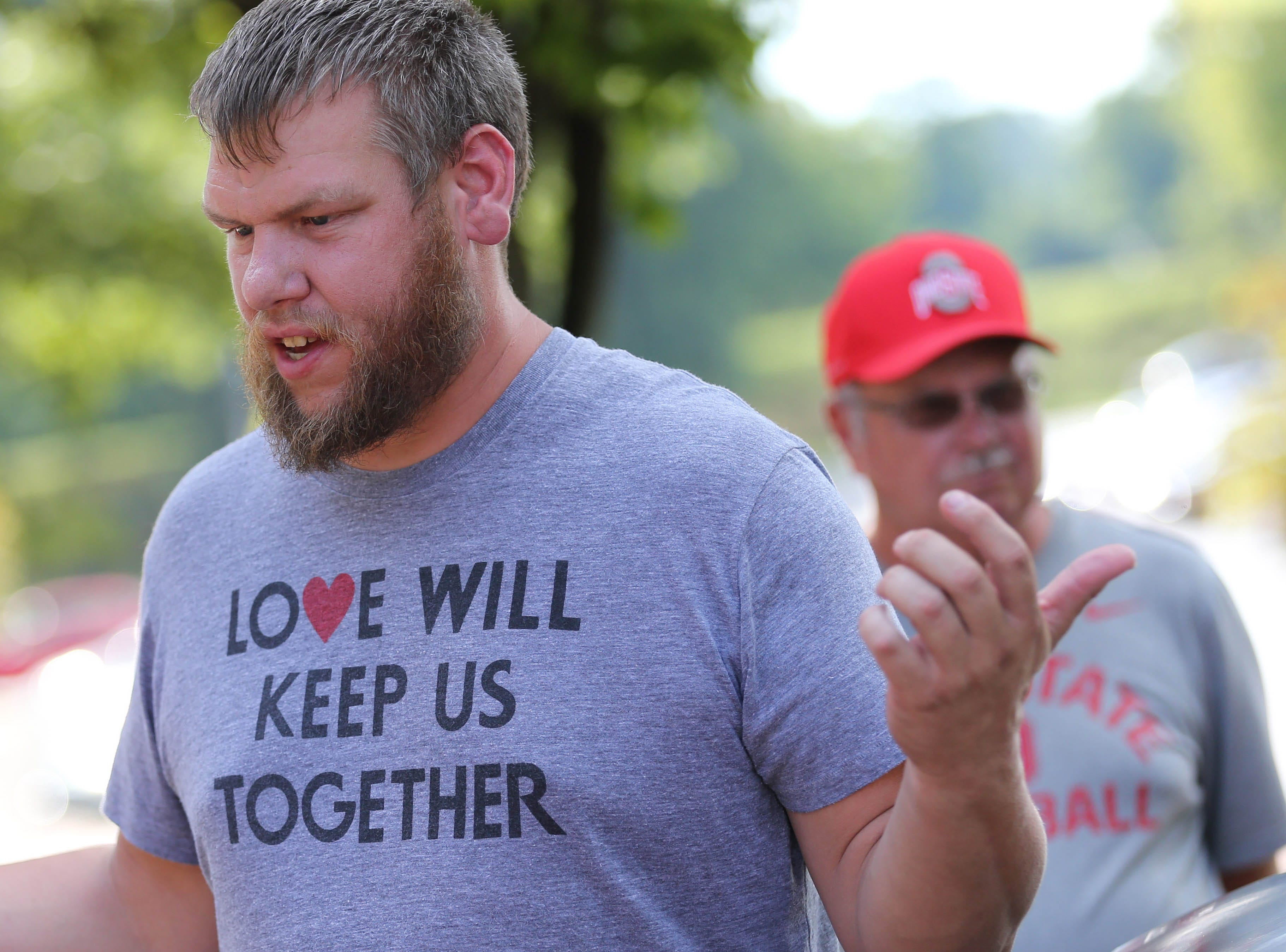 Ryan Donnal speaks with reporters in support of Ohio State coach Urban Meyer at a rally held at Ohio Stadium.